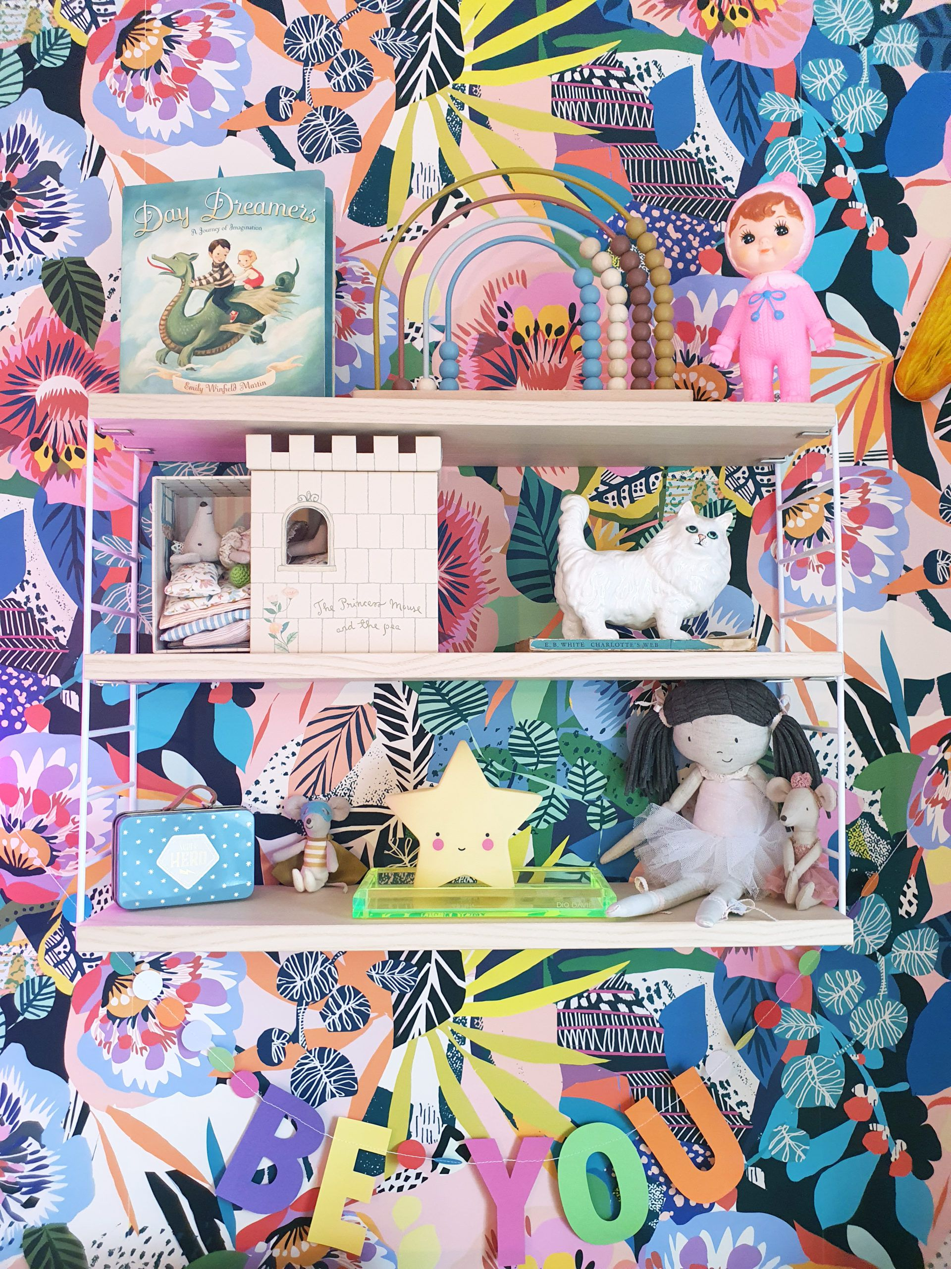 Summer Garden Wallpaper behind shelves with various items and a sign that says BE YOU under the shelves