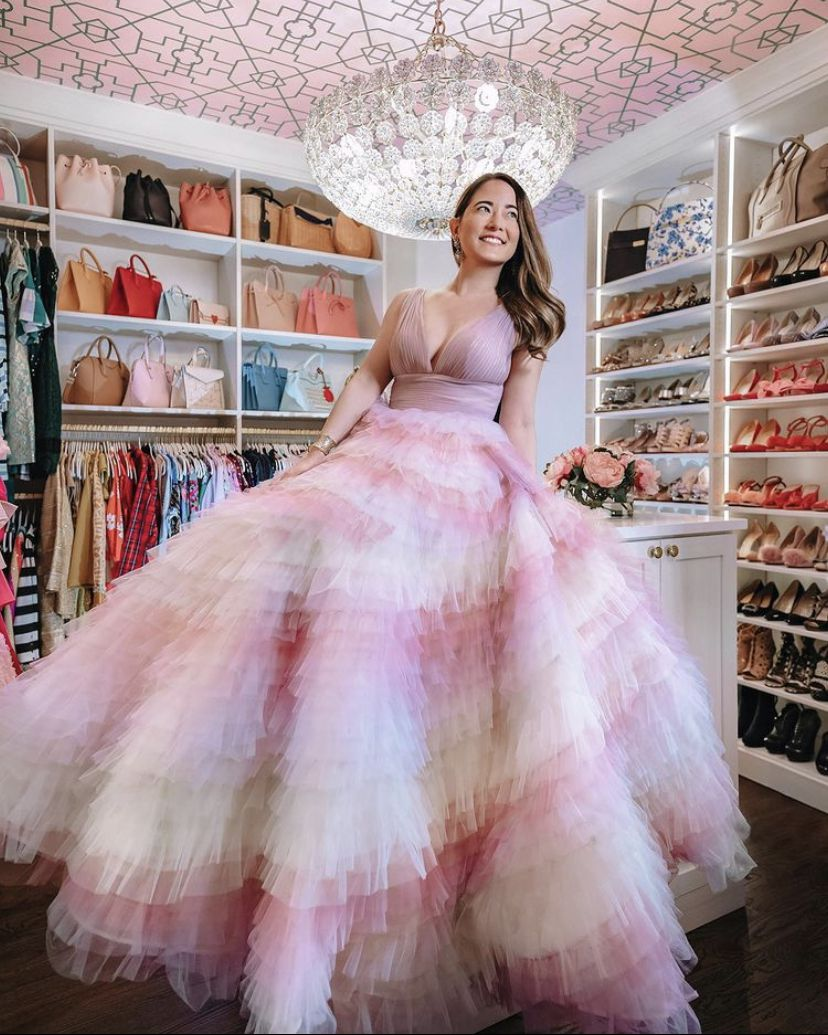 Jennifer Lake from Style Charade posing in a pink dress with a fluffy fair skirt and camisole in her wardrobe closet with a crystal chandelier and pink Trellis Wallpaper by Bethany Linz on the ceiling